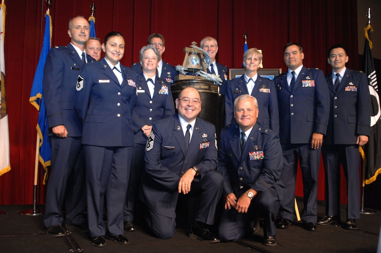 Members of the 452nd Air Mobility Wing, March Air Reserve Base, Calif., along with Command Chief Master Sgt. Agustin Huerta, and Commander, Brig. Gen.l James Melin, front and center, pose with the Raincross Trophy after it was awarded to the 452nd AMW at the 11th Annual Raincross Trophy Dinner held July 23, 2009, at the Riverside Convention Center, Riverside, Calif. The dinner is hosted by the Greater Riverside Chambers of Commerce Military Affairs Committee to honor and recognize the 11 wings and two groups in 4th Air Force.  (U. S. Air Force photo/Senior Master Sgt. Kim Allain)  (released)