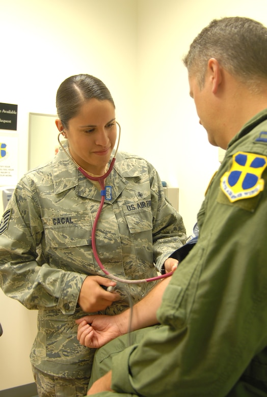 Tech. Sgt. Julianne Cacal, 95th Aerospace Medicine Squadron independent duty medical technician, checks a patient's blood pressure. As an IDMT, Sergeant Cacal diagnoses and treats servicemembers under the license of a supervising doctor. (U.S. Air Force photo/Senior Airman Julius Delos Reyes)
