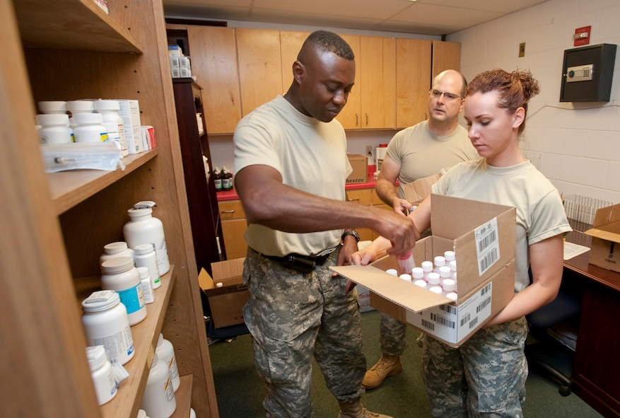 Maj. Alton Stewart from San Antonio Medcom, Capt. Eric Eliason from Camp Mabry Austin, and Sgt Keleigh Estes from Houston Medcom stock the pharmacy at the Raymondville, TX clinic for Operation Lone Star, July 26, 2009. (U.S. Air Force by Tech Sgt Charles Hatton)