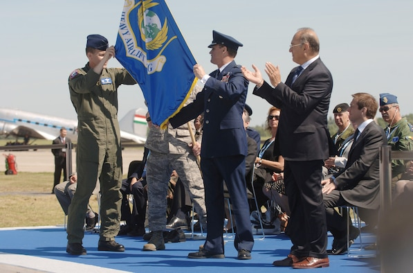 During the official activation ceremony of a first-of-its-kind multinational heavy airlift wing at Papa Air Base, Hungary, July 27, 2009 U.S. Air Force Col. John Zazworsky and Brig. Gen. Richard Johnston unveil the organizational flag. The ceremony celebrated the efforts of the 12 nations who, during the last 10 months, stood up the organization that will provide strategic airlift worldwide for humanitarian, disaster relief, and peacekeeping missions in support of the European Union, United Nations and NATO. (U.S. Air Force photo/Master Sgt. Scott Wagers)