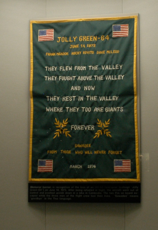 """DAYTON, Ohio -- This banner memorialized the HH-53 helicopter, call sign Jolly Green-64, which crashed in a Cambodian lake on June 14, 1973. The two PJs on board escaped while the three men of the flight crew lost their lives. """"Sawadee"""" means """"goodbye"""" in the Thai language. The banner is on display in the Southeast Asia War Gallery at the National Museum of the U.S. Air Force. (U.S. Air Force photo)"""