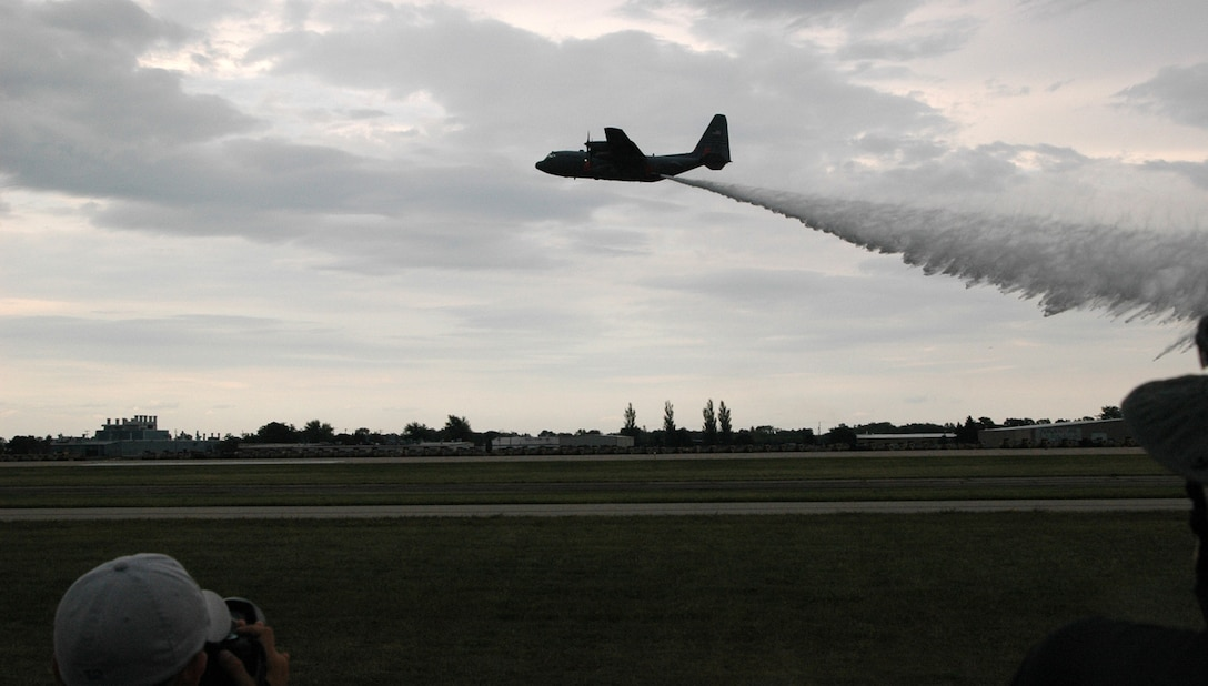An Air Force Reserve C-130 equipped with the Modular Airborne Firefighting System, or 'MAFFS II, presents a live water drop July 27 at the Experimental Aircraft Association AirVenture airshow in Oshkosh, Wis. The airshow is known as the world's greatest aviation celebration and attracts hundreds of thousands of aviation enthusiasts from all over the world. The C-130, assigned to the 302nd Airlift Wing at Peterson Air Force Base, Colo., is equipped with the new MAFFS II system and is on display at EAA AirVenture through July 29. (U.S. Air Force Photo/Capt. Jeff Schoen)