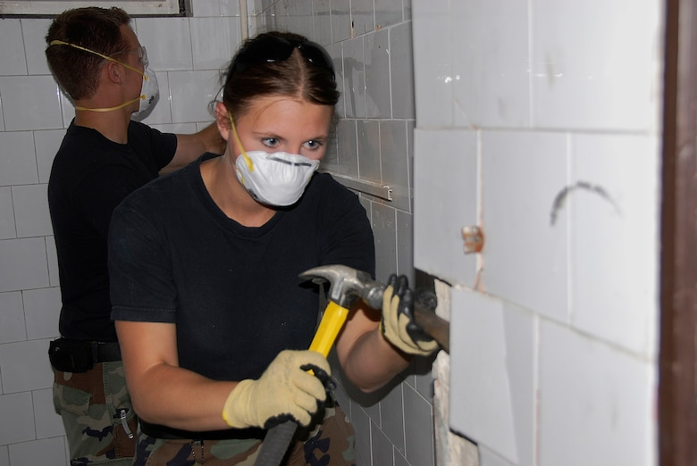 Senior Airman Casandra Pohlen, a member of the 133rd Airlift Wing?s Civil Engineering Squadron, uses a chisel and hammer to break some tile which will be replaced in one of two buildings being renovated by the Squadron in ?jd?r?gd, Hungary on July 21, 2009. About forty Minnesota Airmen are in Hungary for a two week Deployment for Training.  USAF photo by Staff Sgt. Amber Monio.