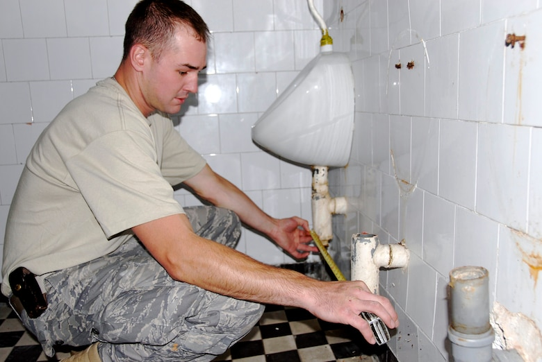 Staff Sgt. Doug Swigart, a plumber in the 133rd Airlift Wing?s Civil Engineering Squadron, obtains measurements in the bathroom of one of two buildings which the squadron is renovating on July 21, 2009. About forty Minnesota Airmen are in ?jd?r?gd, Hungary as part of their two week Deployment for Training. USAF photo by Staff Sgt. Amber Monio.