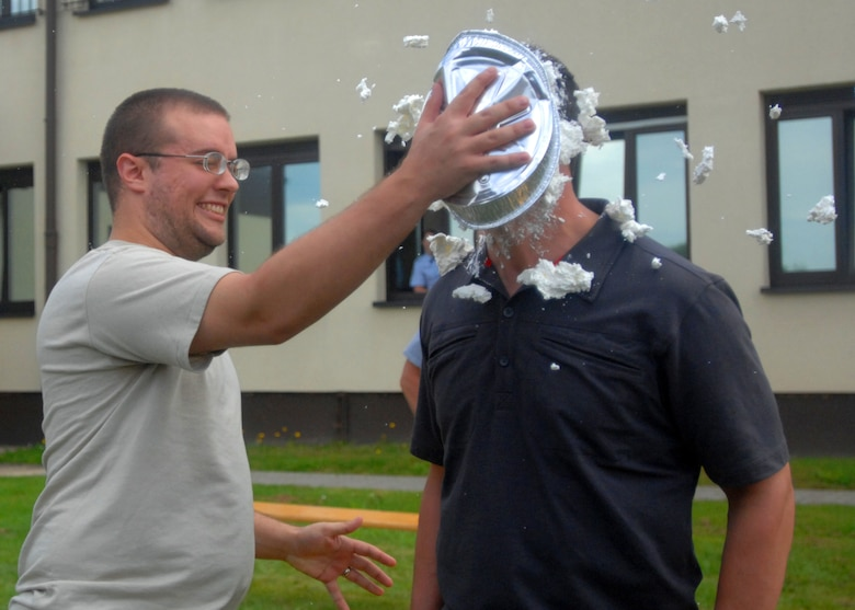 SPANGDAHLEM AIR BASE, Germany -- Senior Airman Steven Underwood, 52nd Operation Support Squadron current intelligence analyst, pies Capt. Ryan Wood, 52nd OSS intelligence weapons officer, in the face during the OSS moral picnic July 27. Once a quarter the 52nd OSS booster club sponsors an event to bring the flights together for a day of friendly competition, food, an inflatable castle, a tug-o-war contest. (U.S. Air Force photo by Senior Airman Jenifer H. Calhoun)