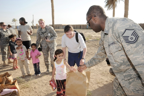 Master Sgt. Shantell Frierson hands an Iraqi child a bag of treats July 24 in Baghdad. Forty-five Airmen and Soldiers volunteered to visit and distribute donated items to local Iraqi families as part of the Sather Air Base Good Neighbor Program. Sergeant Frierson is a Multinational Corps Iraq Joint Crew Composite Squadron automated data processing technician. Sergeant Frierson is deployed from Ramstein Air Base, Germany, and is a native of Coward, S.C. (U.S. Air Force photo/Tech. Sgt. Johnny L. Saldivar)