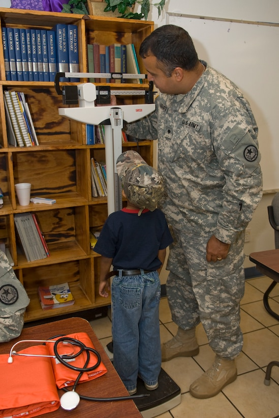 U.S. Army Spc. Eric Enriquez checks the weight of a young patient at the Medical Innovative Readiness Team Site (MIRTS) located at the LaSara Community Resource Center,  LaSara, Texas during Operation Lone Star.  Operation Lone Star is a Joint Civilian/Military Medical mission offering free Medical care to the region, 29 July 2009.(USAF Photo by Master Sgt. Michael Lachman)