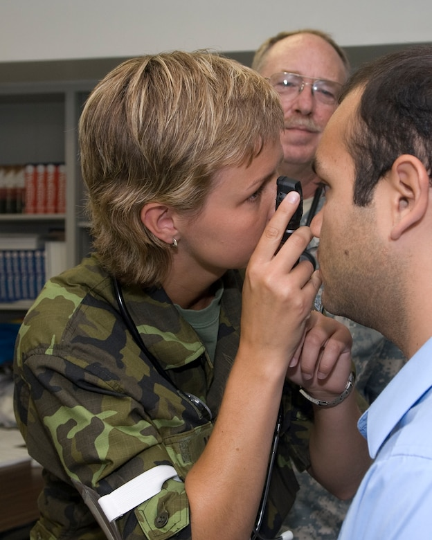 Warrant Officer Marika Bilkova of the Czech Republic Medical Team performs an eye exam while U.S.Army Lt. Colonel Skip Jones watches over her, during Operation Lone Star at Raul A. Besteiro Jr. Middle School. Operation Lone Star is a Joint Civilian/Military Medical mission offering free Medical and Dental care to the region. Brownsville,Texas, July 27, 2009.(USAF Photo by Master Sgt. Michael Lachman)