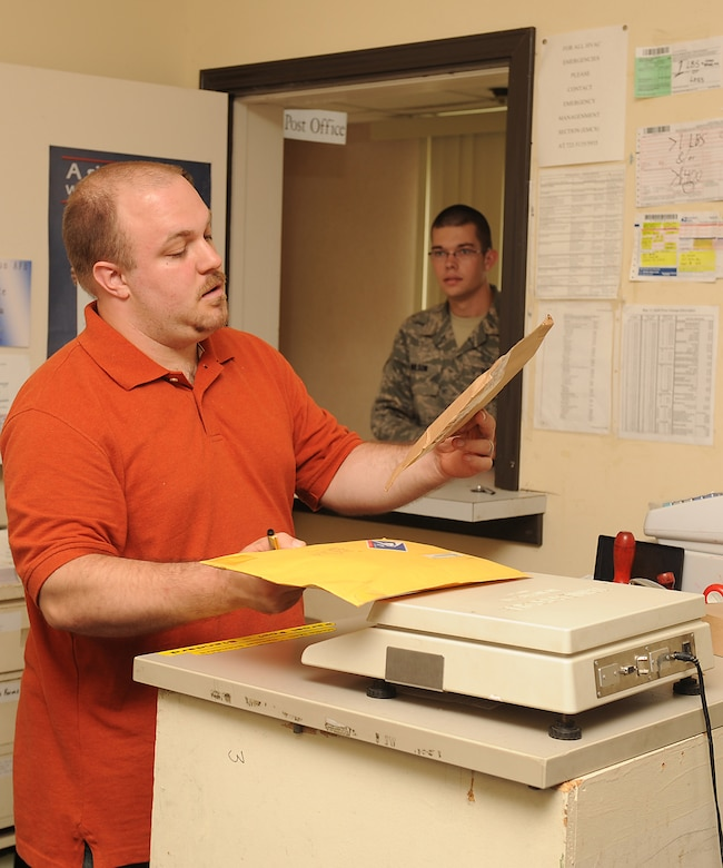 David Medus, U.S. Postal Service clerk, assists Airman Joshua Wilson, 4th Component Maintenance Squadron egress systems apprentice, in shipping packages at Seymour Johnson Air Force Base, N.C., July 24, 2009. The base post office receives approximately 800 packages and 1,500 letters weekly. (U.S. Air Force photo by Airman 1st Class Whitney S. Lambert)