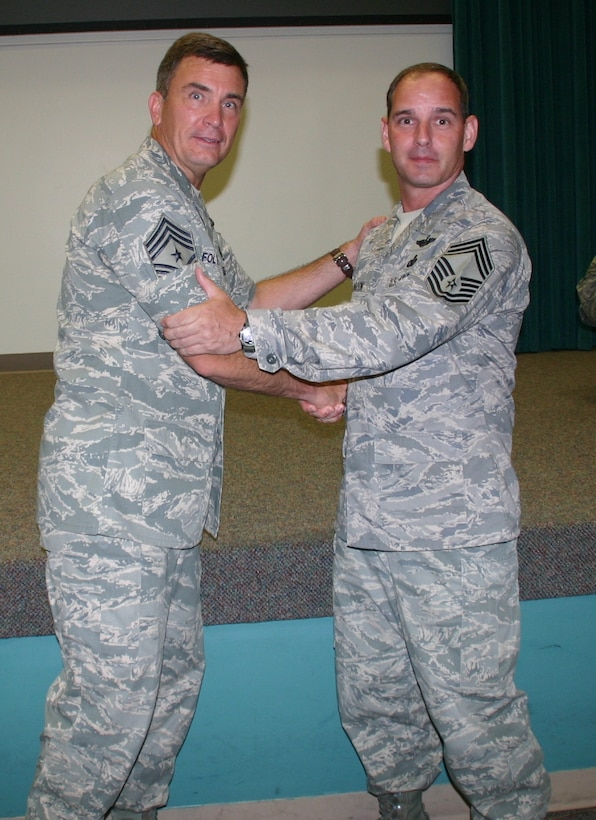 Chief Master Sgt. James Foltz, outgoing command chief, 552nd Air Control Wing, congratulates the incoming command chief, Chief Master Sgt. Scott Magoon, on becoming the wing's new enlisted leader. Photo courtesy of 1st Lt. Kinder Blacke.