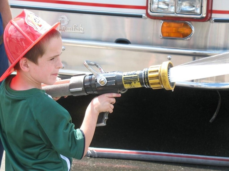 Benjamin Hall, 7, son of Master Sgt. Eric Hall, handles a firehouse as part of a demonstration by Bradley Rescue during Space and Aviation Day July 18, 2009, at Bradley ANG Base, East Granby, Conn.  The demonstration was one of many aimed to attract participants to the fund-raising event organized by Bradley Family Day, Inc.  (Photo courtesy of Master Sgt. Eric Hall)