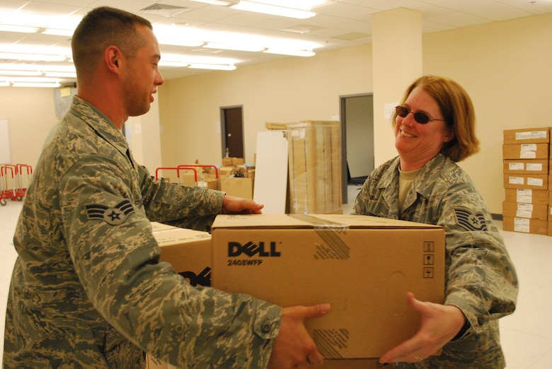 Senior Airman Sean Vaclavik and Tech. Sgt. Dara Febres, communications computer systems craftsmen, 103rd Air and Space Operations Group, receive a shipment of mission critical computer equipment for the new Combined Air Operations Center facility in Southwest Asia May 29, 2009.  The Airmen deployed as part of an eight-member team focused on enhancing command and control capabilities for Air Force operations in theater.  (U.S. Air Force photo by Lt. Col. Reid Christopherson)