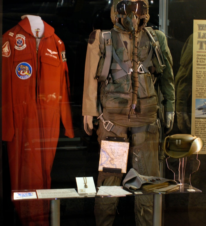 """DAYTON, Ohio - Artifacts in the First In, Last Out: Wild Weasels vs. SAMs exhibit: 1) King's 100 Mission patch which he obtained during his second tour in 1972. 2) King's good luck Buddha charm which he carried on his missions. 3) Copy of mission line-up card from King's end of tour mission flown on May 14, 1969 in the museum's F-105. Line-up cards gave aircrews basic information about the mission such as radio call signs and weapons load out. 4) King's carry-on map and checklist bag. 5) King's bush hat with """"counters"""" (missions over North Vietnam)marked on the front and """"non-counters"""" (all others) marked on the back. 6) King's party suit and flight suit. (U.S. Air Force photo)"""