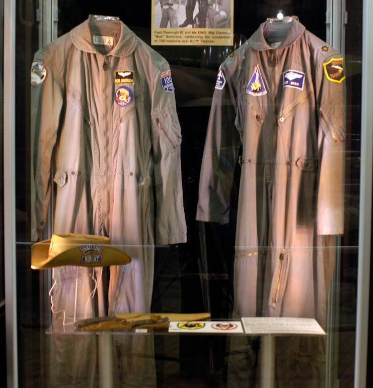 """DAYTON, Ohio - In the First in, Last Out: Wild Weasels vs. SAMs exhibit 1) Capt. Robert Dorrough's K-2B flight suit and """"boonie hat"""" from his service as a Wild Weasel pilot at Korat from June 1967 to January 1968. On his hat are hash marks showing each mission, with the red marks denoting missions in Route Pack 6. Although new aircrews were supposed to have low-threat orientation missions to start their tours, Dorrough's first mission was near Hanoi. 2) Maj. Arthur Oken's K-2B flight suit from his service with the 354th TFS of the 355th TFW at Takhli in 1969-1970. Oken flew as a Wild Weasel EWO in F-100Fs, F-105Fs and F-105Gs. In his three tours, he flew over one hundred Wild Weasel combat missions (including about 20 F-100F missions in Route Pack 6. 3) Knife and machete carried by Dorrough on all his missions. He bought the handmade machete while in survival school in the Philippines. 4) Patches, the F-105 Wild Weasels in the 388th Tactical Fighter Wing at Korat were in one squadron. It was first designated the 13th Tactical Fighter Squadron and later the 44th TFS. (U.S. Air Force photo)"""