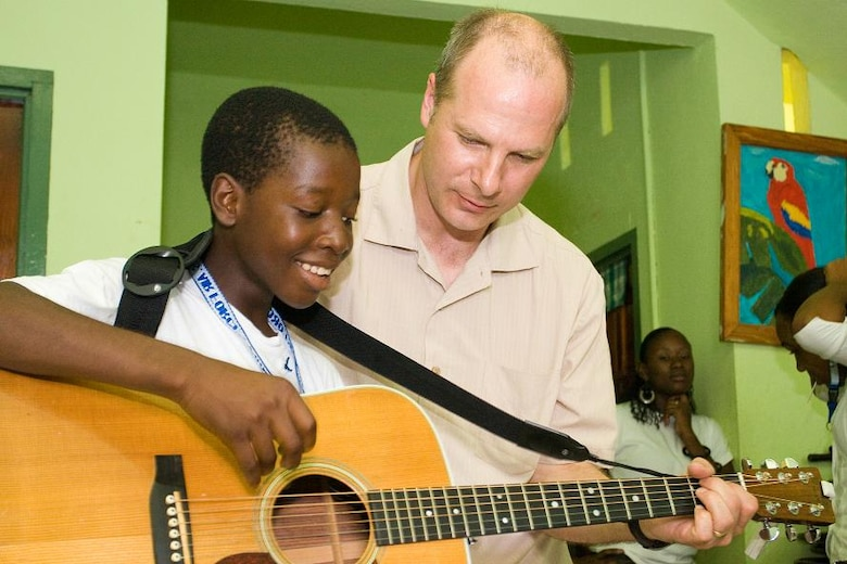 "VICTORIA, Grenada -- Tech Sgt. Stephen Brannen, a guitar player with the Air Force Academy Band ""Blue Steel,"" instructs an orphan at Father Mallaghan's Home for Boys in Victoria, Grenada June 1.  Blue Steel spent the day with boys at the home before performing a public concert in the center of the village.  The community outreach event is part of Operation Southern Partner, an Air Forces Southern-led event aimed at strengthening partnerships with nations in the U.S. Southern Command area of focus through mil-to-mil subject matter exchanges.  In addition to the exchange program, Airmen also had the opportunity to volunteer at various charitable and community organizations in each host nation.  (Photo courtesy of Sagar Pathak of HorizontalRain.com)"