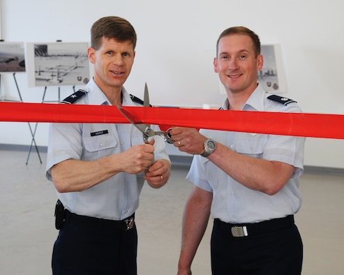 Brig. Gen. Mark W. Graper, 354th Fighter Wing commander, and Lt. Col. Gregory Church, 353rd Combat Training Squadron commander, ceremoniously cut the ribbon to make the opening of the new RED FLAG-Alaska operations and maintenance facility official. The project was a year long, $12 Million conversion of an outdated aircraft maintenance back shop. (U.S. Air Force photo/Airman 1st Class Willard E. Grande II)