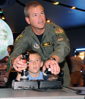 """Pilot in training, Cooper Hirst of Ogden Utah, gets a little help with the controls of a Flight Simulator from 466th Fighter Squadron pilot, Lt. Col. Buster Delmonte, before the showing of the IMAX movie """"Fighter Pilot: Operation Red Flag"""" at the Clark Planetarium in Salt Lake City during Air Force Week Salt Lake City on June 2. (U.S. Air Force photo by Alex R. Lloyd)"""