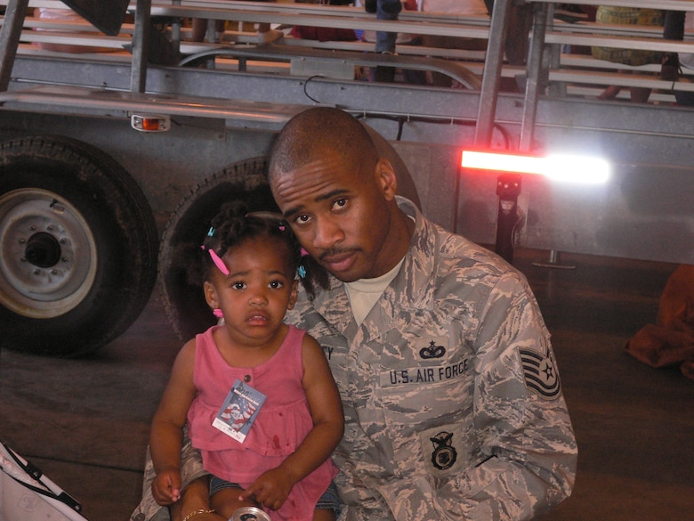 """BUCKLEY AIR FORCE BASE, Colo. -- Tech. Sgt. Imari Motley, non-commissioned officer in charge of physical security with Detachment 3 Aerospace Data Facility-Colorado, poses in a photo with his daughter, Imaiya.  Sergeant Motley is Team Buckley's Warrior of the Week for May 29- June 4.  """"My most memorable personal accomplishment is my family because without their support I wouldn't be where I am today.  I know that no matter how hard times get I can rely on them."""" (Courtesy Photo)"""
