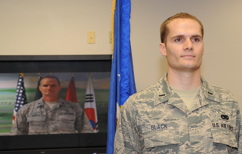 Then-1st Lt. Travis Black, 87th Logistics Readiness Squadron Materiel Management Flight commander,  prepares to take the oath of office administered by his father, Lt. Col. Steven Black, chief of nutritional medicine at Bagram Air Base, Afghanistan, via video teleconference May 29. Captain Black and his family had not seen the lieutenant colonel since he deployed four and a half months ago. (U.S. Air Force photo/Staff Sgt. Danielle Johnson)
