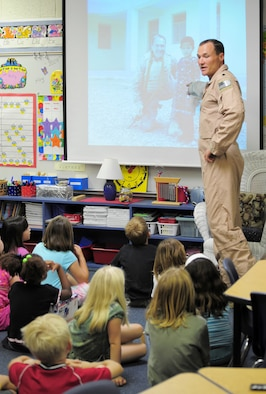 Lt. Col. Joe Alcorn, an HH-60G Pave Hawk pilot, speaks to his son's 2nd grade class at Gemini Elementary in Melbourne Beach, Fla. Colonel Alcorn and other reservists from the 920th Rescue Wing, Patrick Air Force Base, Fla., spent four months in Afghanistan supporting joint operations. Colonel Alcorn showed the class images of an Afghan school he visited. The Afghani children received school supplies donated by the 2nd graders. (U.S. Air Force photo/Master Sgt. Rob Grande)