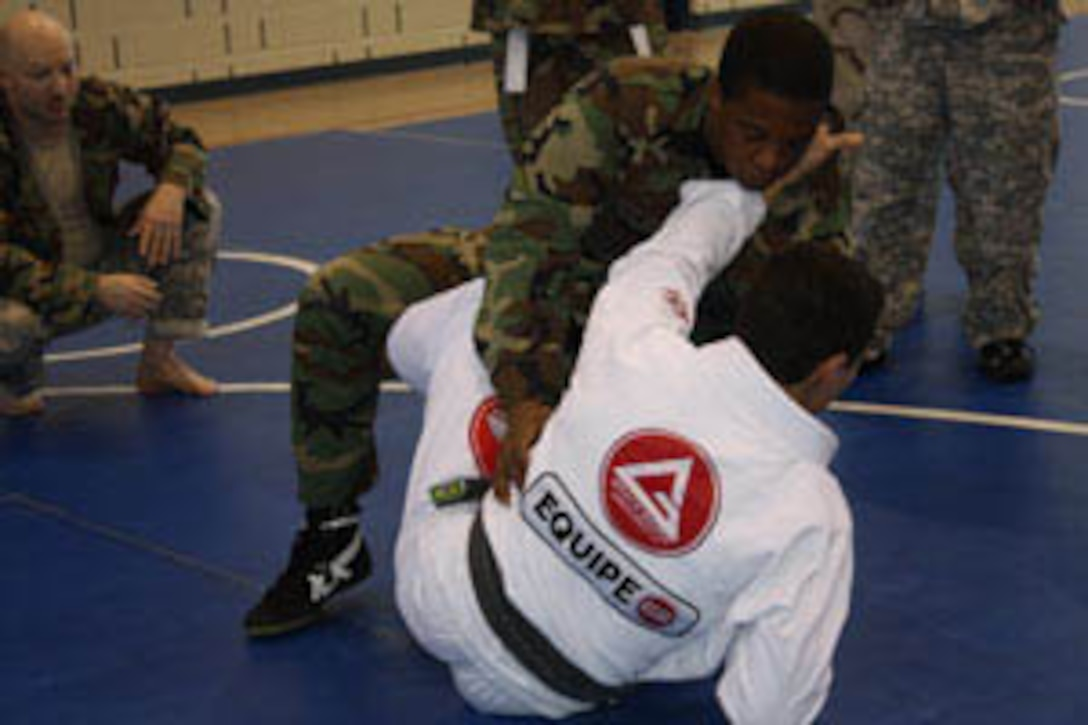 Professor Marcos Barros (in white), a black belt in Gracie Ju Jitsu, teaches combative techniques to SSgt Ruel Taylor of the 110th AOG while Army Spc David Kirby looks on.  Barros was visiting as a guest instructor during classes held at the 129th RTI facilities in Springfield, IL.