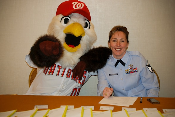 Senior Master Sgt. Jennifer Hutcherson, First Sergant with the 69th Aerial Port Squadron and the 459th Air Refueling Wing yellow ribbon program coordinator welcomes reservists with Screech, the mascot from the Washington Nationals baseballl team at the registration table at the 459th ARW Yellow Ribbon welcome home event.