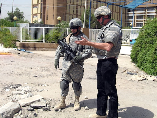 Bob Perry and Capt. Christian Thompson assess the damage done to a high voltage electrical line while deployed in support of Operation Iraqi Freedom in July 2007.  The line, which leads to a children's hospital, was damaged by an improvised explosive device. Earlier this year, Air Force senior leaders outlined their vision for supporting Department of Defense civilians to serve in global expeditionary positions through a program called the Civilian Expeditionary Workforce. (Courtesy photo)
