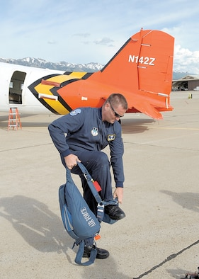 Lt. Col. Aldru Aaron, commander of the 98th Flight Training Squadron Air Force Parachute Team, steps into his parachute rig before a jump over Salt Lake City into Spring Mobil Ballpark for Airman's Opener Air Force Night with the Salt Lake Bees. (U.S. Air Force photo by Todd Cromar)