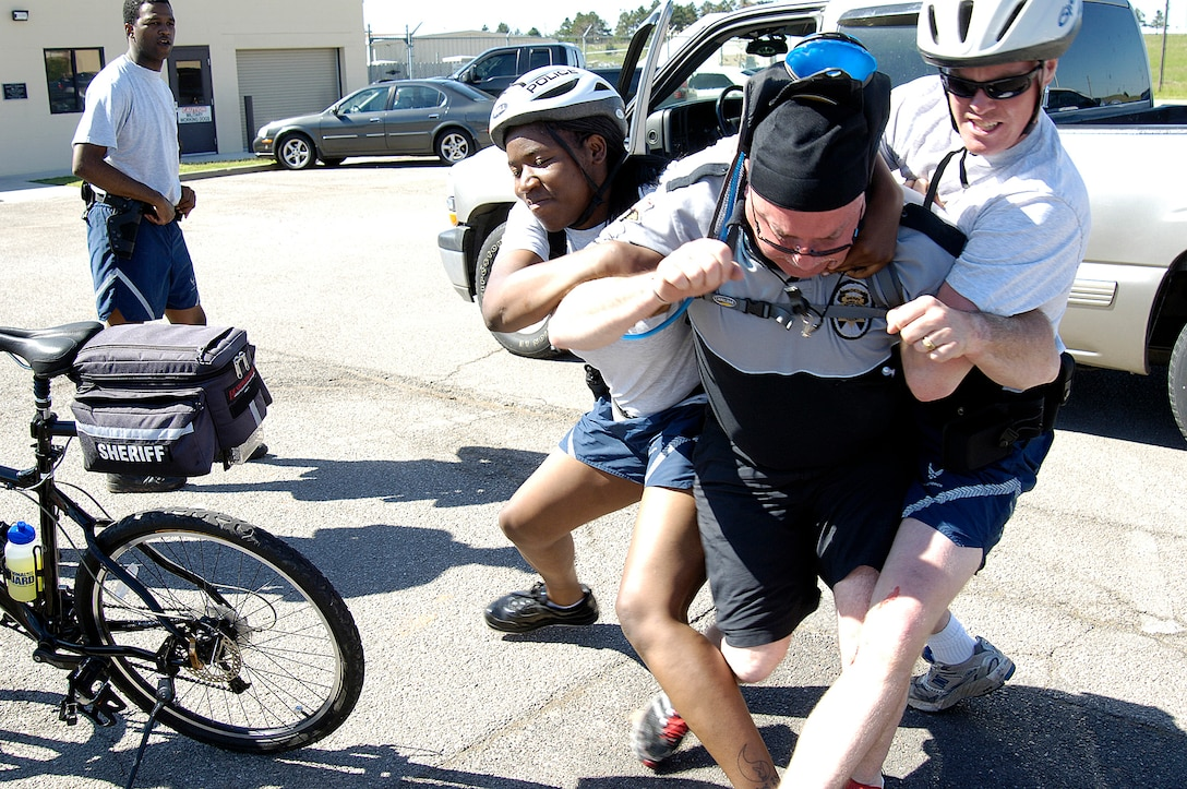 """Oklahoma County Sheriff's deputy Bob Camp struggles to run from 72nd Security Forces Squadron Airmen 1st Class Argentina Andrews and Brett Christenson during a training scenario for Tinker's """"bike cops."""" The two-day course taught how to turn the bicycle's maneuverability into a public relations and crime fighting asset. (Air Force photo/Margo Wright)"""