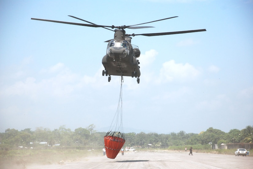 A CH-47 Chinook helicopter from Joint Task Force-Bravo at Soto Cano Air Base, Honduras, takes off with a Bambi bucket to fight a fire in National Park Jeannette Kawas near Tela, Honduras, June 3. The Chinook made 35 runs in all -- dropping more than 60,000 gallons of water to douse the flames in the national wildlife preserve that was inaccessible by ground. (U.S. Air Force photo/Tech. Sgt. Rebecca Danet)