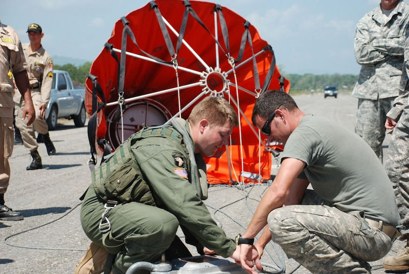U.S. Army Sgts. Sidney Scott (left) and Michael Marquis, Joint Task Force-Bravo, work to attach a Bambi Bucket to a CH-47 Chinook helicopter to fight a forest fire near Tela, Honduras, June 3.  In all, the flight crew made 35 runs -- dropping more than 60,000 gallons of water on the blaze in a national wildlife reserve.  (U.S. Air Force photo/Tech. Sgt. Rebecca Danét)