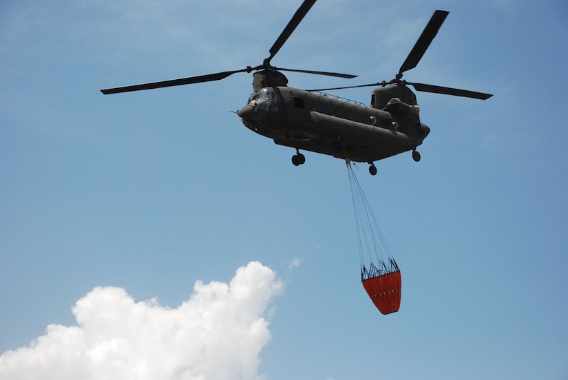 A CH-47 Chinook helicopter from Joint Task Force-Bravo at Soto Cano Air Base, Honduras, prepares to drop 2,000 gallons of water on a fire in National Park Jeannette Kawas near Tela, Honduras, June 3.  The Chinook made 35 runs in all -- dropping more than 60,000 gallons of water to douse the flames in the national wildlife preserve that was inaccessible by ground.  (U.S. Air Force photo/Tech. Sgt. Rebecca Danét)