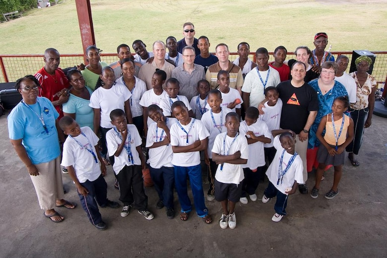 """VICTORIA, Grenada -- Caretakers, children, volunteers and Airmen from the U.S. Air Force Academy Band """"Blue Steel"""" pose for a group photograph in Victoria, Grenada, June 1.  Blue Steel spent the day with orphans from Father Mallaghan's Home for Boys before performing a public concert in the center of the village.  The community outreach event is part of Operation Southern Partner, an Air Forces Southern-led event aimed at strengthening partnerships with nations in the U.S. Southern Command area of focus through mil-to-mil subject matter exchanges.  In addition to the exchange program, Airmen also had the opportunity to volunteer at various charitable and community organizations in each host nation.(Photo courtesy of Sagar Pathak of HorizontalRain.com)"""