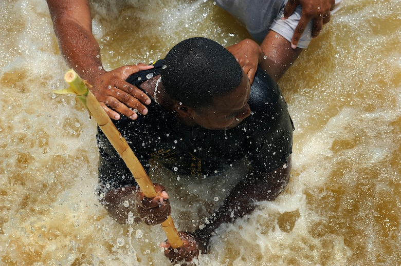"""Constable Damon Kangal of the Royal St. Lucia Police Force's Special Service Unit leads a team in a """"wedge"""" formation while practicing swift-water rescue procedures that were taught by U.S. Air Force pararescuemen June 5 during Operation Southern Partner at La Toc, St. Lucia. Operation Southern Partner is a long term commitment between U.S. and partner nations to share experiences, information, vital skills, tactics and techniques in preparation for future regional challenges that require cooperative solutions.  (U.S. Air Force photo/Staff Sgt. Bennie J. Davis III)"""
