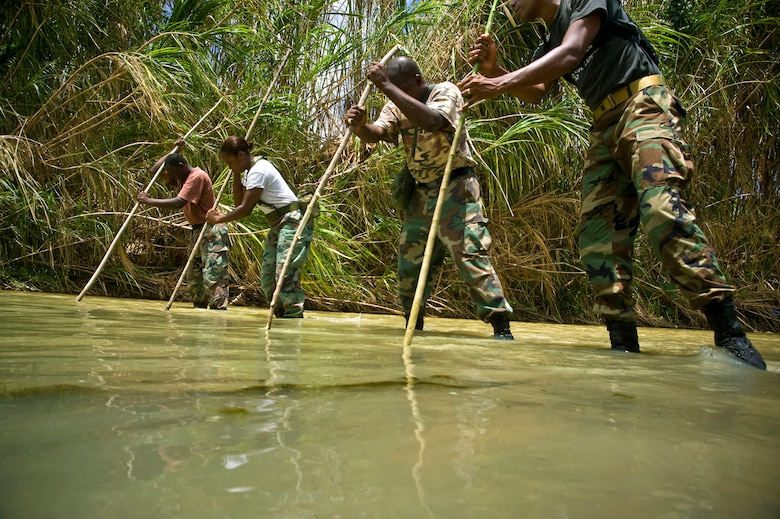 Members of the Royal St. Lucia Police Force's Special Service Unit make their way across a stream using measuring sticks while learning swift-water rescue procedures being taught by U.S. Air Force pararescuemen June 5 during Operation Southern Partner at La Toc, St. Lucia.  Operation Southern Partner is a long term commitment between U.S. and partner nations to share experiences, information, vital skills, tactics and techniques in preparation for future regional challenges that require cooperative solutions.  (U.S. Air Force photo/Staff Sgt. Bennie J. Davis III)