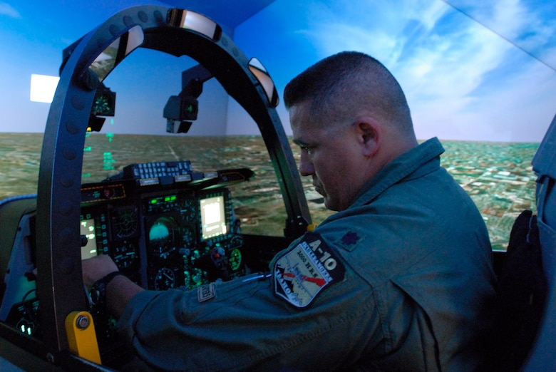 Lt. Col. Anthony  Brown of the 190th Fighter Squadron, conducts training on the upgraded A-10C Full Mission Trainer (FMT). The (FMT) simulator mimics the real-world A-10C with fully operational hands-on controls and instrument panel, providing pilots with a safe and realistic training environment. (U.S. Air Force photo/Staff Sergeant Robert Barney. RELEASED)