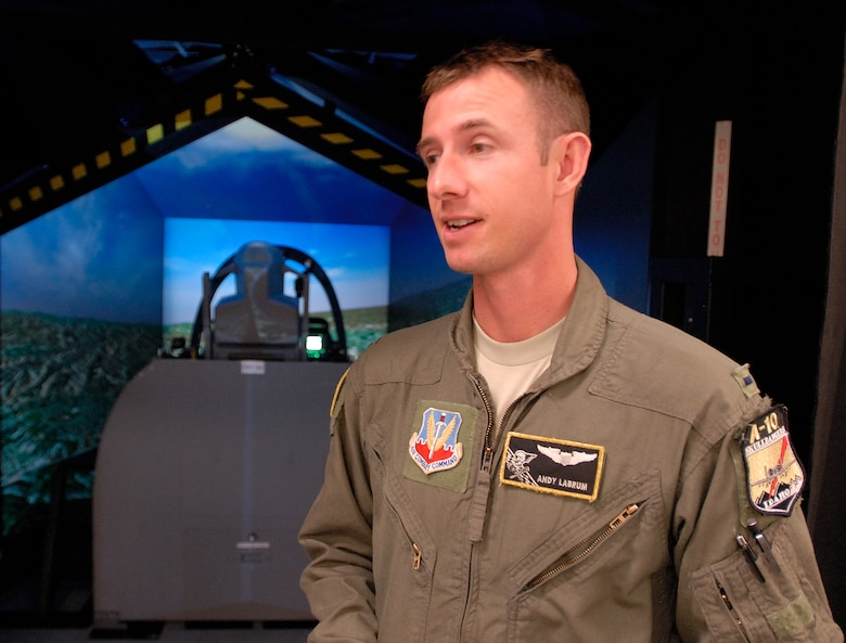 1st Lt. Andrew Labrum, of the 190th Fighter Squadron, explains the recent upgraded A-10C Full Mission Trainer (FMT). The (FMT) simulator mimics the real-world A-10C with fully operational hands-on controls and instrument panel, providing pilots with a safe and realistic training environment. (U.S. Air Force photo/Staff Sergeant Robert Barney. RELEASED)