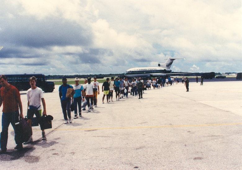 ANDERSEN AIR FORCE BASE, Guam - Refugees stream from chartered aircraft after evacuating Clark Air Base, Philippines, June 1991.  More than 21,000 refugees were flown to Andersen in less than one week.  The Military Airlift Command alone airlifted 15,000 passengers on 246 missions; the others came in on chartered flights. (Courtesy photo).