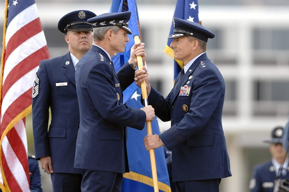 Lt. Gen. Michael Gould (right) accepts the U.S. Air Force Academy guidon from Gen. Norton Schwartz, chief of staff of the Air Force, during a change of command ceremony at the Academy June 9.  General Gould, a class of '76 Academy graduate, returns as the 18th superintendant, replacing Lt. Gen. John Regni, who is retiring.  Academy Command Chief Master Sgt. John Salzman waits to secure the unit flag following the exchange. (U.S. Air Force photo)
