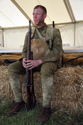 Lance Cpl. Alex Maze, 21, comptroller at Marine Corps Base Quantico, Va., sits down and rests on a bale of hay after shooting part of the National Museum of the Marine Corps reenactment video of the Battle of Belleau Wood June 9. The Marines were fully decked out in WWI unifroms and weapons.