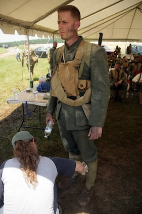 Sgt. Michael Howard, 24, stands and receives his make-up treatment before filming the next segment of the National Museum of the Marine Corps reenactment video of the Battle of Belleau Wood June 9. The Daytona Beach, Fla., native was one of 40 Marines selected from Marine Corps Base Quantico, Va., to take part in the filming.