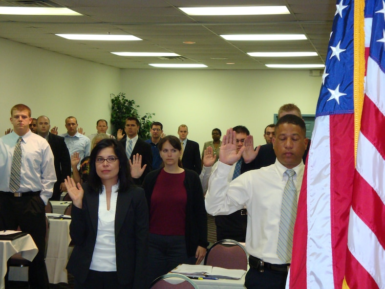 A group of more than 30 civilians raise their hands as part of the process to officially become federal employees.  After a period of training, the new hires, most with advanced degrees, will become contracting specialists working for various contracting organizations here. (Air Force photo by Ron Fry)
