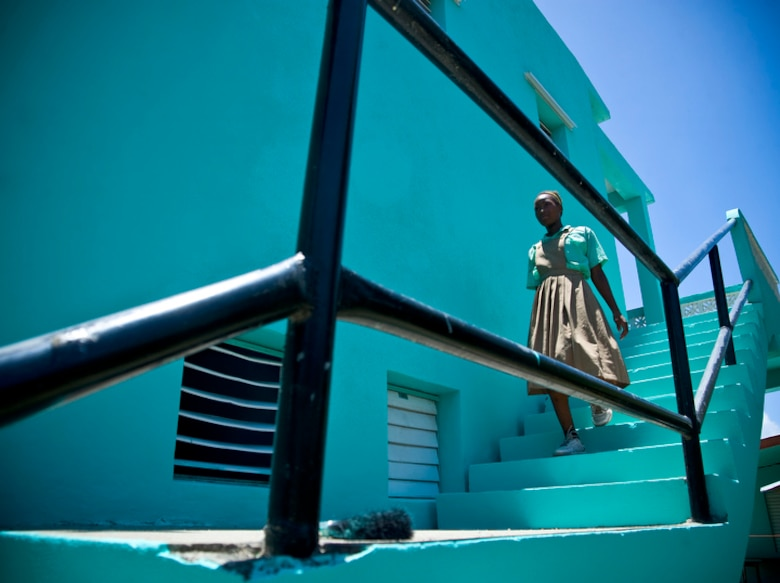 A young school girl makes her way down freshly painted stairwell at the Stella Maris School for the Physically Disabled June 8 in Belize City, Belize. Airmen deployed here for Operation Southern Partner spent the day painting the school exterior. (U.S. Air Force photo/Staff Sgt. Bennie J. Davis III)