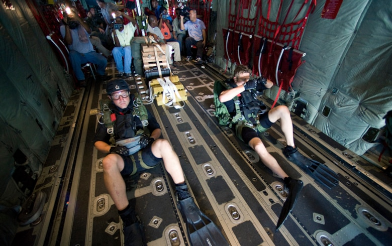 On board a C-130J Hercules, Capt. Travis Shepard, a combat rescue officer (left), and Senior Airman Brandon Smith, a pararescueman, prepare to demonstrate a rigged alternate method zodiac, or RAMZ, capability jump into the Caribbean Ocean June 9 for members of the Belize National Coast Guard and local media during Operation Southern Partner. (U.S. Air Force photo/Staff Sgt. Bennie J. Davis III)