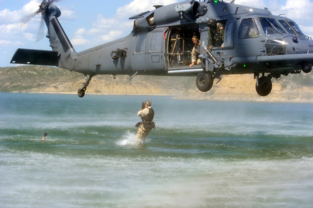 Staff Sgt. Kevin Myerscough enters the water after jumping from an HH-60G Pave Hawk while Master Sgt. Michael Atkins gives the safe thumbs-up and Senior Airman Brent Moore provides oversight June 3 near Laughlin Air Force Base, Texas. The members of the 48th Rescue Squadron from Davis-Monthan AFB, Ariz., were participating in Exercise Resolute Angel in preparation for the upcoming hurricane season. (U.S. Air Force photo/Master Sgt. Heather Cabral)