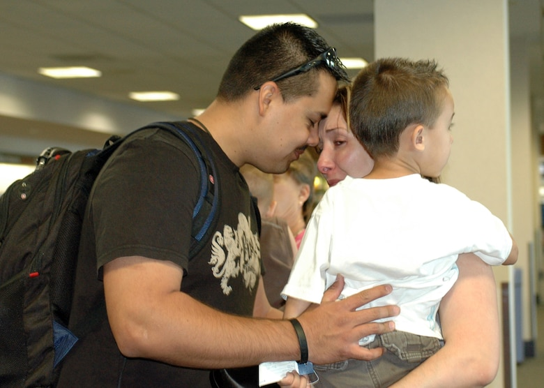 Staff Sgt. Santos Flores bids farewell to his wife Yvette and his son Andres at Tucson International Airport on his way to Al Dhafra Air Base in the United Arab Emirates, June 8. He left with nine fellow Guardsmen from the 162nd Fighter Wing's force support squadron to provide food, fitness, lodging and recreation services to U.S. military members deployed to the area. The group is scheduled to return to Tucson in November. The deployment is Sergeant Flores' first. (Air National Guard photo by Tech. Sgt. Desiree Twombly)