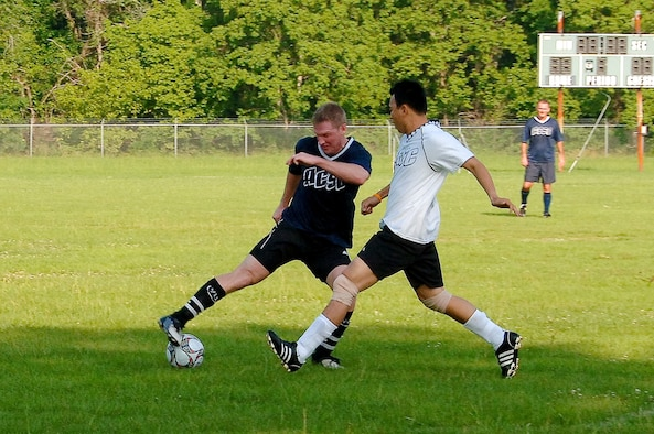 """The Spaatz Center's Air Command and Staff College fielded two soccer teams in this year's intramural play. ACSC 1 and ACSC 2 survived all others to meet for the championship Monday morning. ACSC 1 beat ACSC 2 with a score of 4-1 to take the title. Shown in blue is ACSC 1's Maj. Jason """"Ox"""" Rueschhoff working against ACSC 2's Maj. David Dovo of Argentina. (U.S. Air Force photo/Donna Burnett)"""