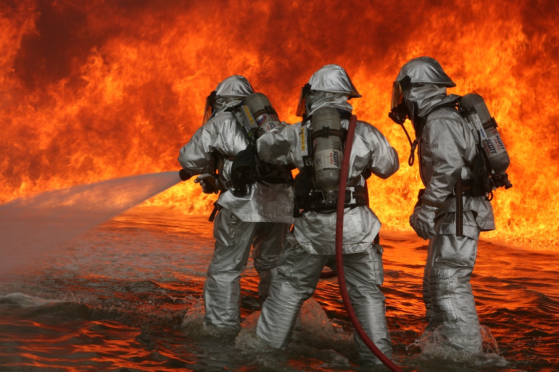 Aircraft Rescue and Firfighting Marines aboard Marine Corps Air Station Miramar fight blazing fires during a simulated fire training exercise at the ARFF Training Pit here. These Marines suited up in 35 pounds of gear needed to combat the overwhelmingly hot blazes June 13-14.