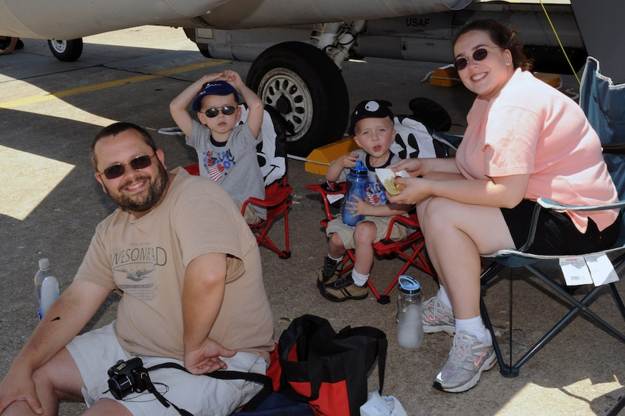WARRENSBURG, Mo. - The Harrison family of Knob Noster, Mo., rest under the wing of an F-15 during the Wings Over Whiteman Air Show and Open House June 6.  Other aircraft on display include; A-10, civilian planes from the University of Central Missouri and Kansas State University, F-22, and an Apache helicopter. (U.S Air Force photo/Senior Airman Jason Huddleston)