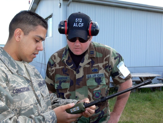 Staff Sgt. Jonathan Concepcion shows Capt. Cliff Cunningham how to program a radio used to monitor several frequencies at once. Both Reservists are from the 512 Airlift Control Flight from Dover AFB Del. The 512 ALCF provided airfield operations for transient aircraft during Maple Flag Exercise 42 at Cold Lake AB Alberta Canada. (U.S. Air Force photo/2nd Lt Joe Simms)